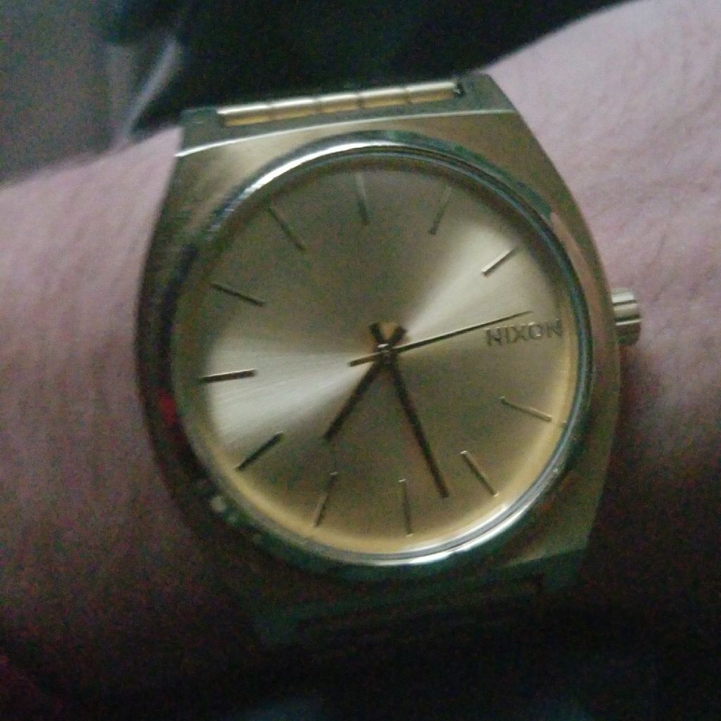 Gold Nixon time teller watch