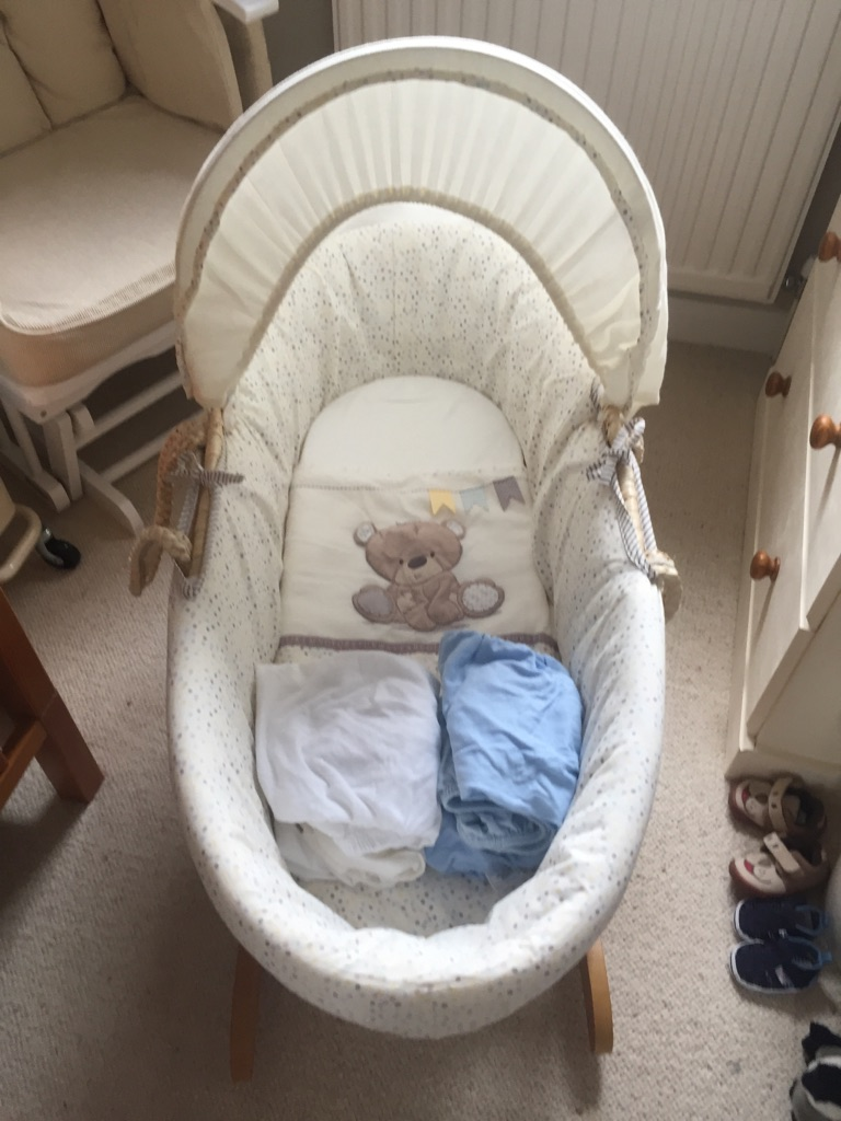 Moses basket, rocking stand and six Moses basket sheets.