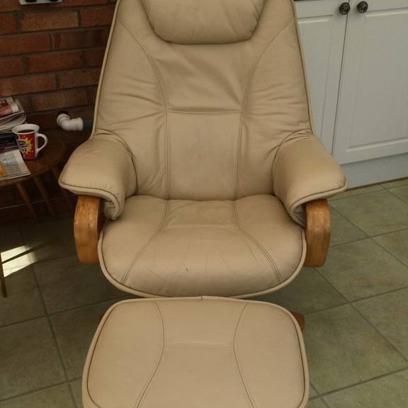 Cream faux leather recliner and footstool