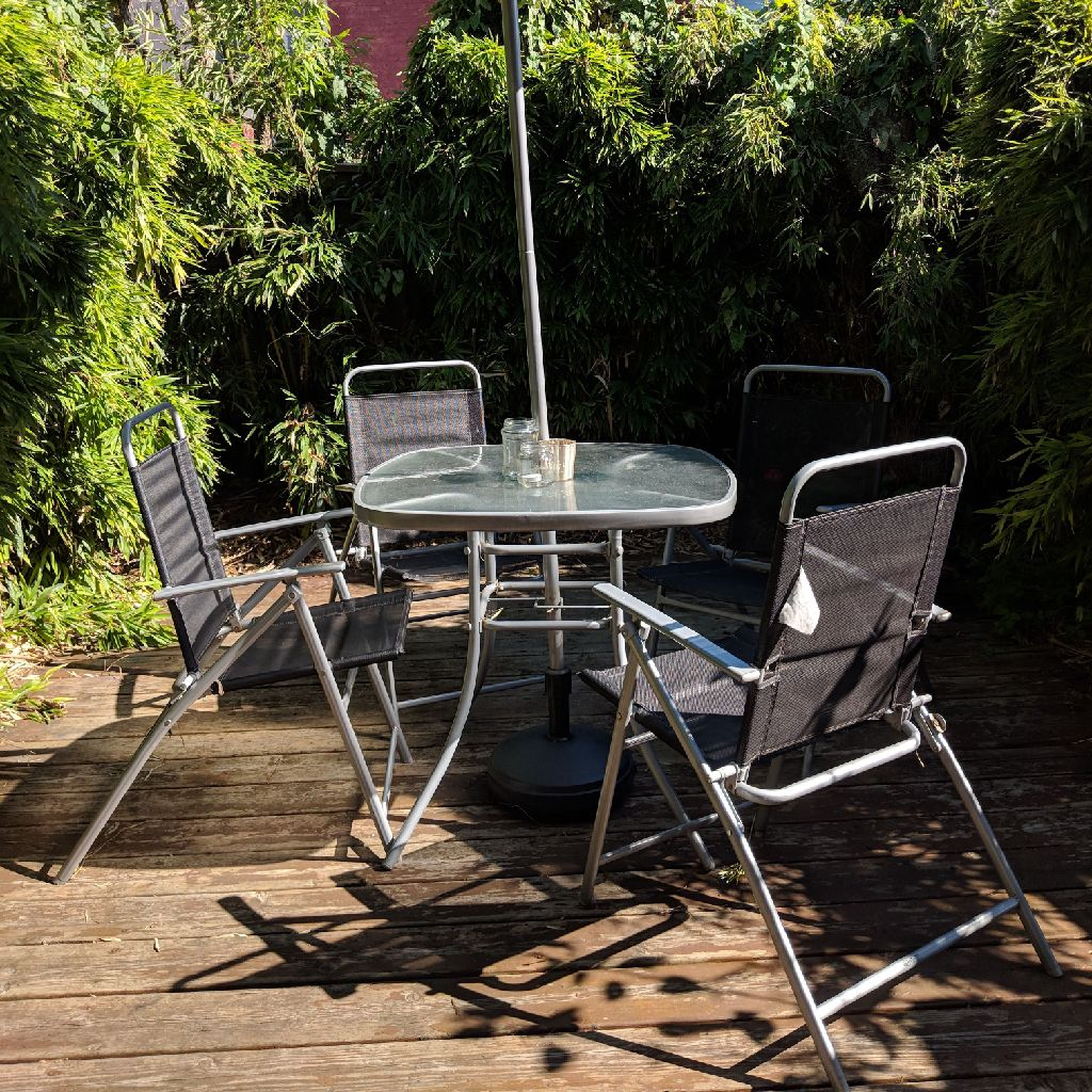 Grey/black garden table set with frosted glass top, parasol and 4 folding chairs