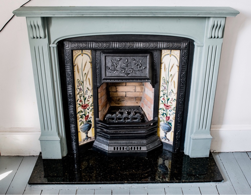 Cast iron fireplace with polished granite hearth and wooden surround