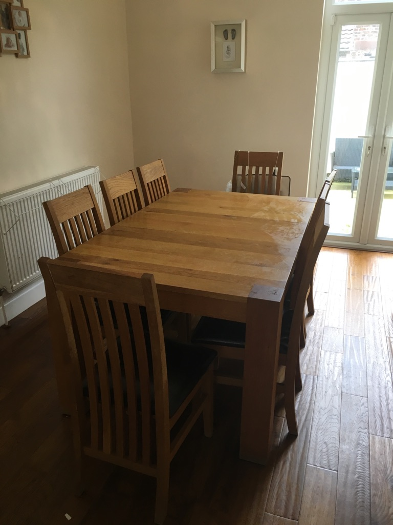 Harvey's solid wood extending table. 8 leather cushioned chairs included. Paid £1800