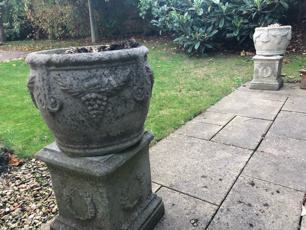 Two ornate stone plant pots