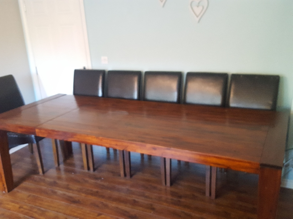 Extending solid wood dining table can seat up to 14