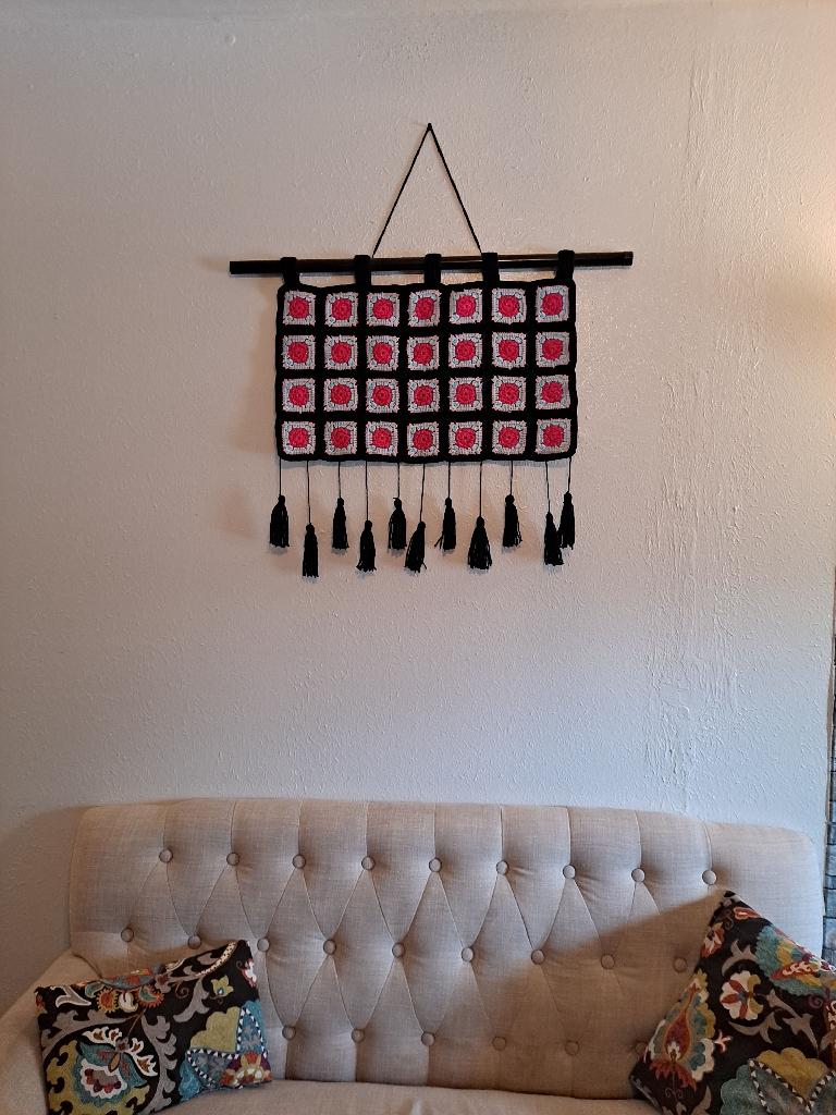 Crochet rectangular granny square wall art with enchanting flower garden in center