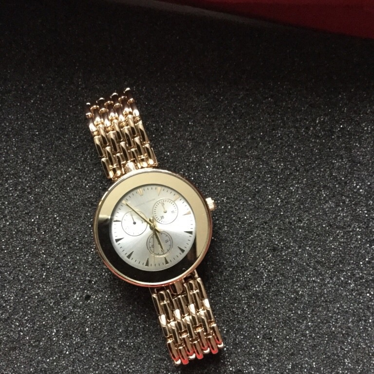 Round gold analog watch with gold link bracelet.