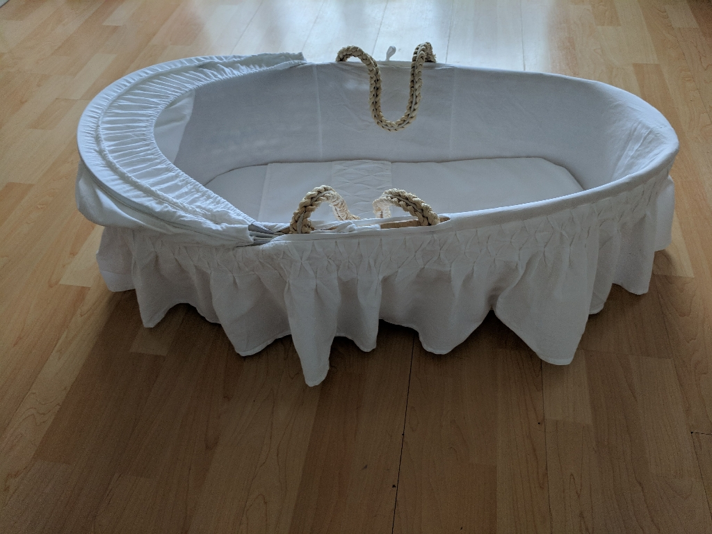 White Moses basket, rocking stand, extra covers and sheets.