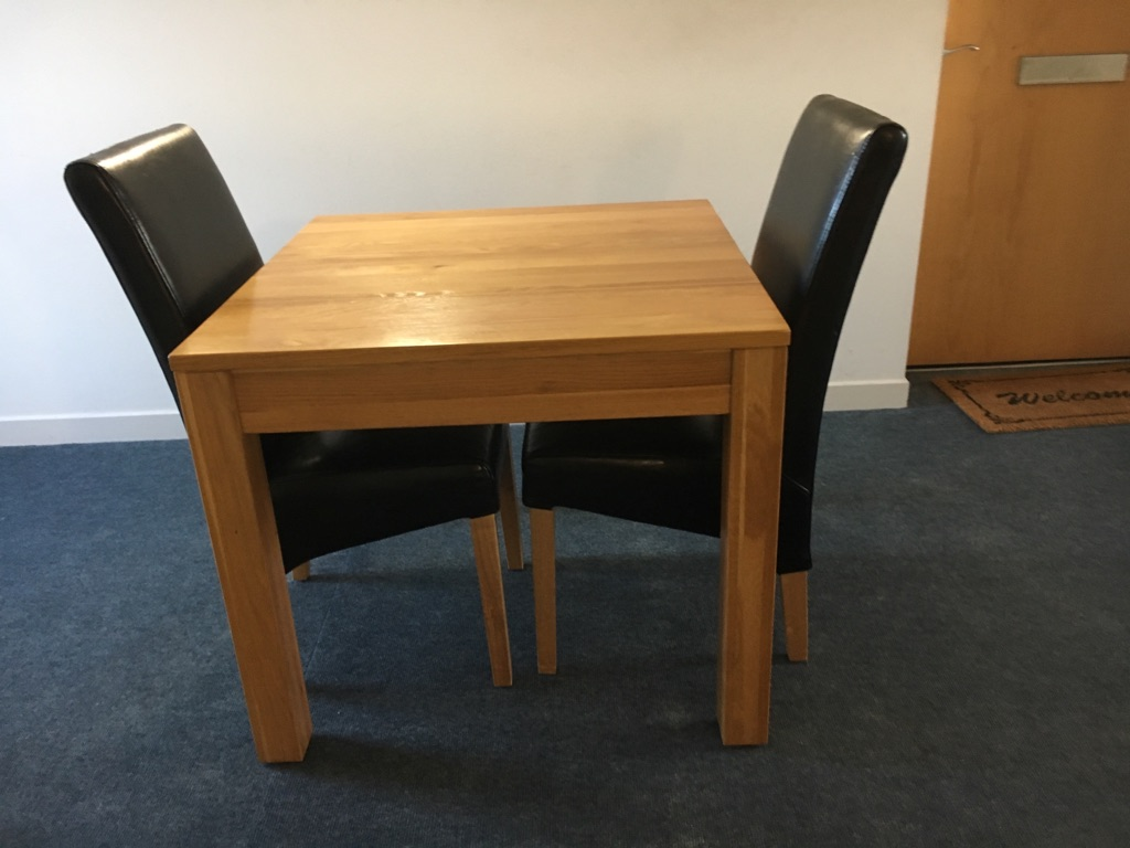 Wooden table with 2 black chairs