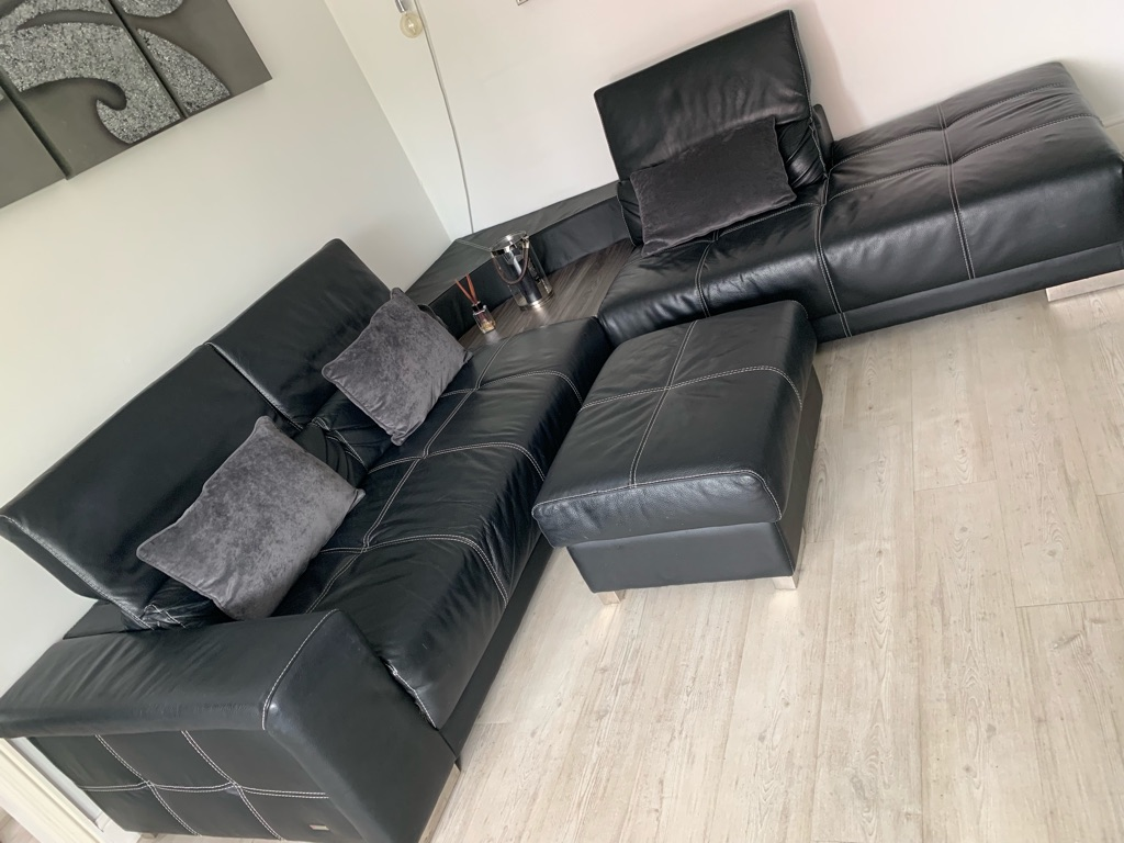 Black corner sofa with side table