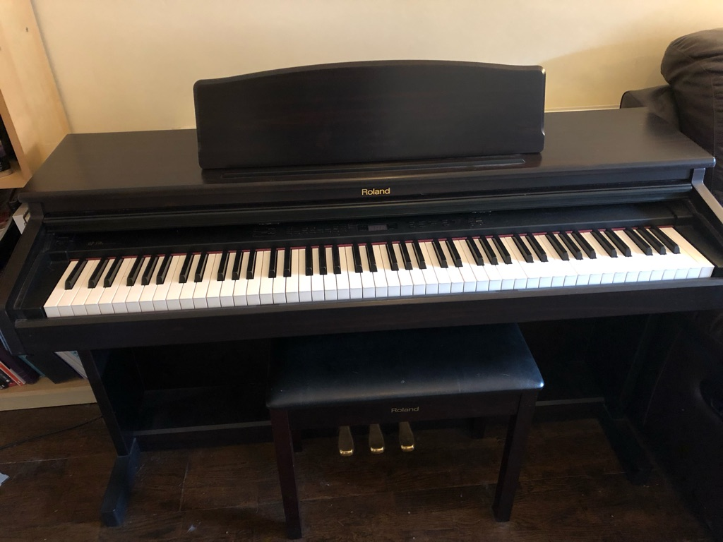 Roland electric piano HP330E with matching stool and new beginners books in excellent condition