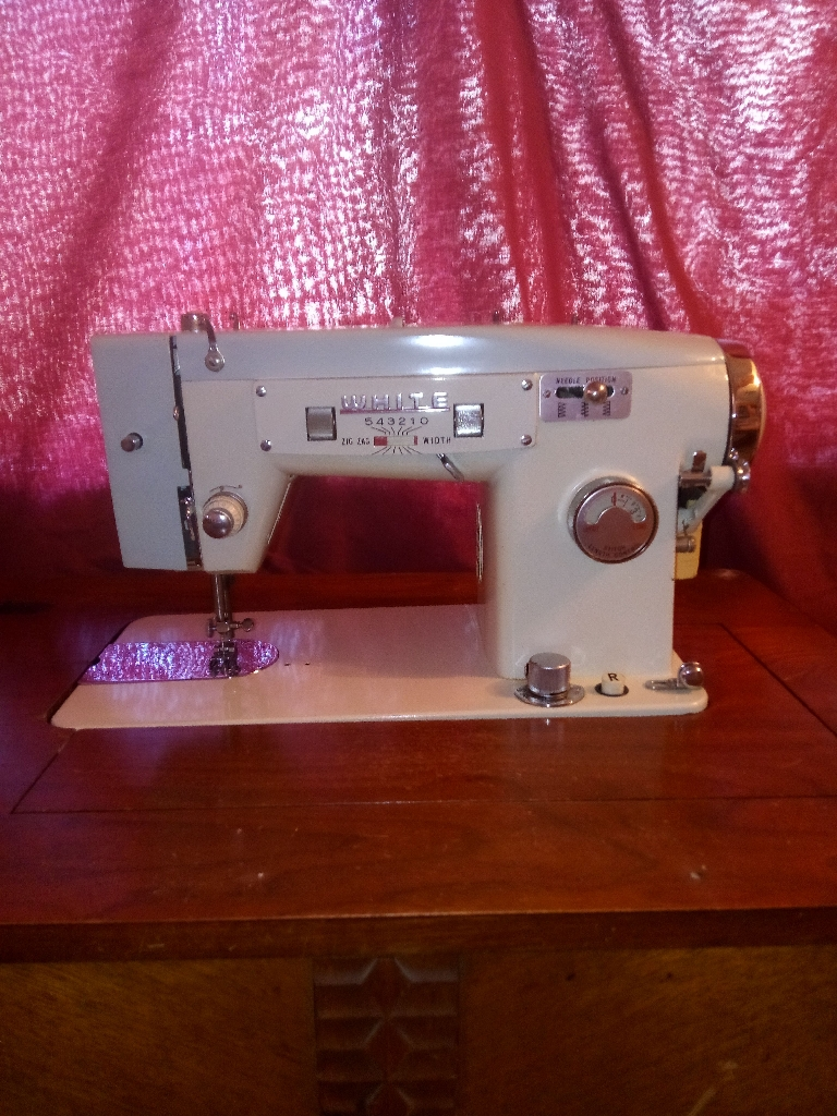 White brand sewing machine in wood cabinet