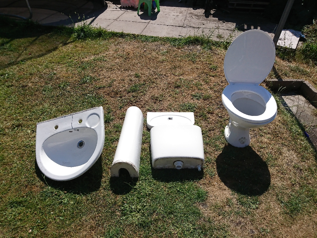 Bathroom toilet, cistern, sink and pedestal in white.