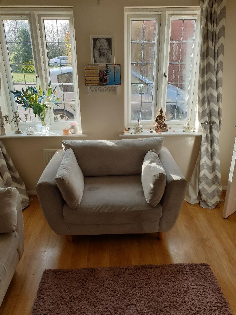 Grey fabric sofa and cuddle chair .