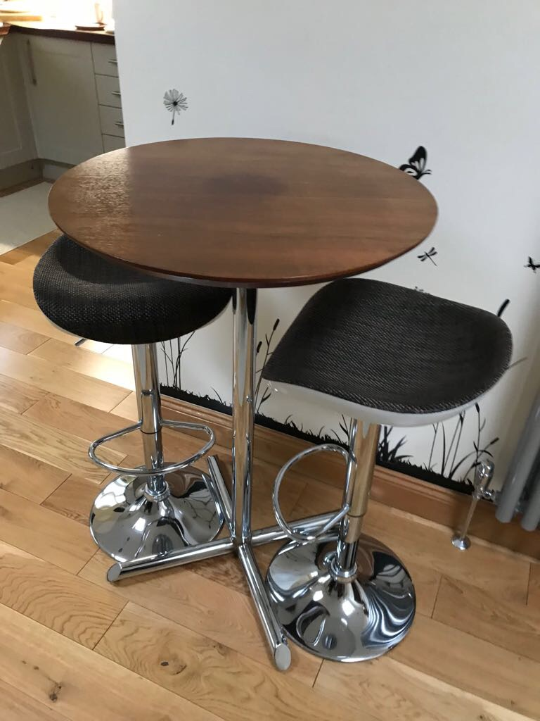 Tall wooden table with bar stools