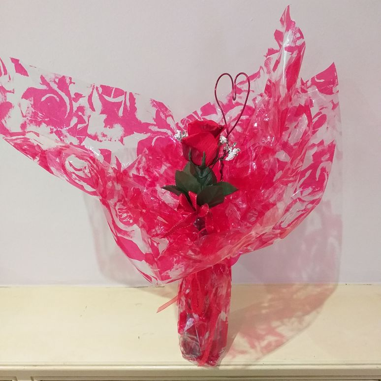 Single silk red rose in glass vase