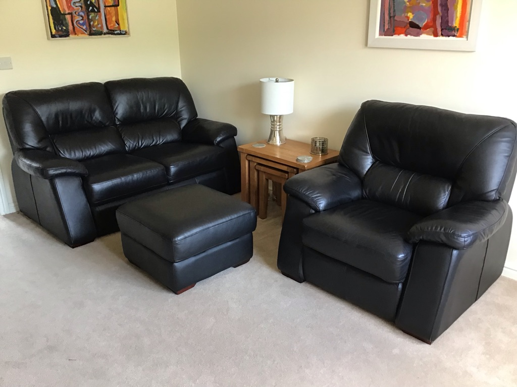 2 Seater black leather sofa (Width 170cm), chair (W109cm) and square storage footstool (62cm).
