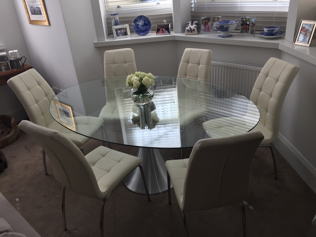 Oval glass dining table with 8 chairs.