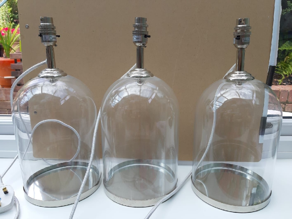3 glass-based lamps with chrome fittings.