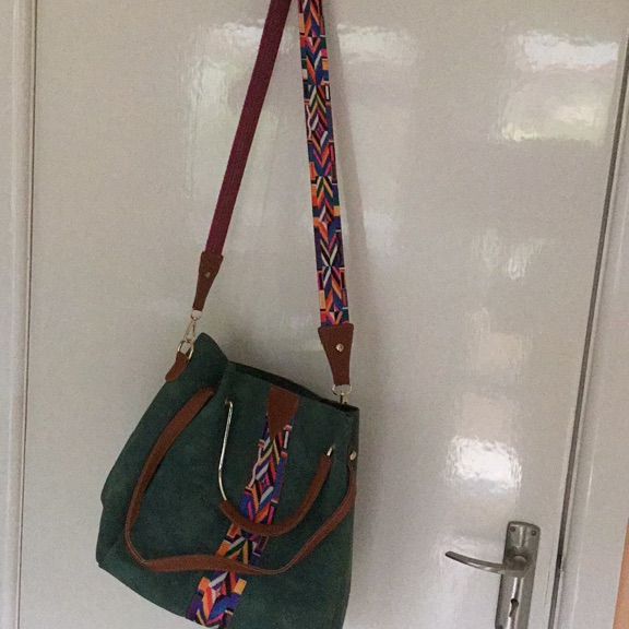 Large, green suede effect slouch bag with detachable colourful strap