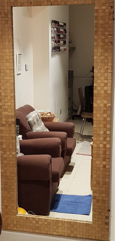 A tall mirror with a rattan border.