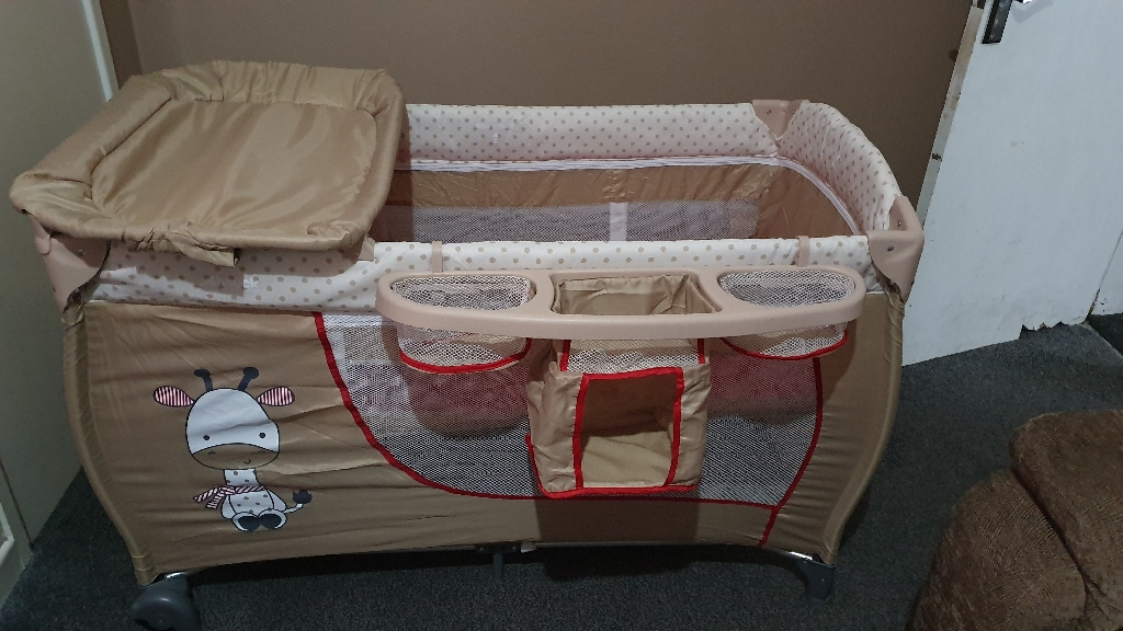 Travel cot with changing area and nappy holders also mattress can be raised to use from new born