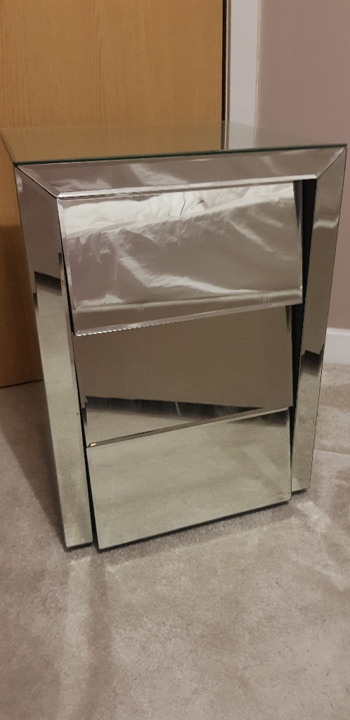 A PAIR OF GLASS SLANTED BEDSIDE TABLES WITH 3 DRAWERS
