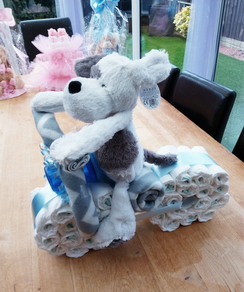 Adorable fluffy dog on a bike Nappy cake, contains approx 36 nappies, two baby blankets, sippy cup, and gorgeous cuddly toy. All gift wrapped in cellophane and blue ribbons. An amazing gift for baby shower, new arrival, Christening. From smoke free home.