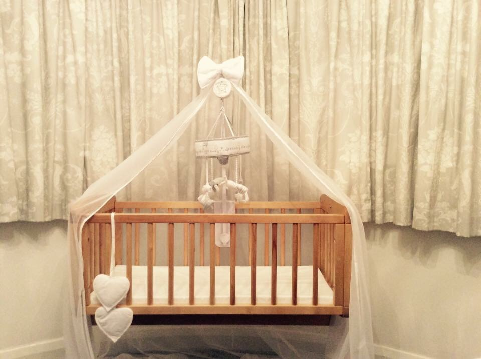 Rocking crib with mobile and decorative netting